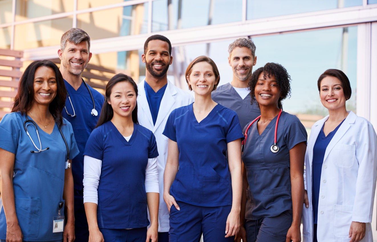 Smiling medical team standing together outside a hospital